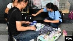 7-13光復上水反水貨客遊行期間,仍有陸客在上水廣場的商場外打開行李箱收拾貨品,以奶粉及日用品為主。(美國之音湯惠云)