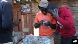 FILE: In this photo taken Thursday, Aug. 8, 2019, vendors are seen on their mobile phones while selling cash in Harare, Zimbabwe. With inflation soaring and cash in short supply, many Zimbabweans transfer funds using their mobile phones and pay a premium to get currency.(AP Photo
