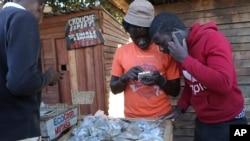 In this photo taken Thursday, Aug. 8, 2019, vendors are seen on their mobile phones while selling cash in Harare, Zimbabwe. (AP Photo/Tsvangirayi Mukwazhi)