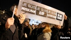 "People hold a placard which reads ""I am Muslim, I am Jewish, I am Catholic, I am Charlie"" at a vigil, following the shooting of 12 people at the satirical newspaper Charlie Hebdo, at the Place de la Republic in Paris, Jan. 8, 2015."
