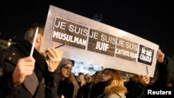 "People hold a placard which reads ""I am Muslim, I am Jewish, I am Catholic, I am Charlie"" at a vigil, following the shooting at the satirical newspaper Charlie Hebdo, Jan. 8, 2015."
