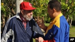 Former Cuban leader Fidel Castro and Venezuela's President Hugo Chavez (R) speak in Havana in this June 28, 2011 handout photo. Supporters of Chavez hailed the release of new footage of the socialist leader as evidence he was recovering from surgery in Cu