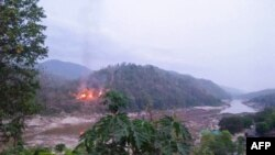 This handout from Kawthoolei Today taken and released on April 27, 2021 shows fires burning at a Myanmar military base along the bank of the Salween river, as seen from Mae Sam Laep town in Thailand's Mae Hong Son province, after the base was attacked and
