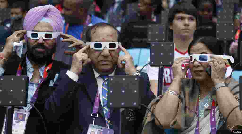 Acting Indian Olympic Association President Vijay Kumar Malhotra (C), his wife Krisha Malhotra (R) and guest Gurmit Singh (L) of India try on their glasses as they sit in the VIP box before the opening ceremony of the London 2012 Olympic Games