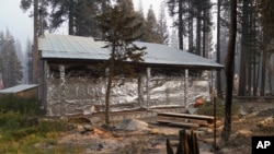 FILE - In this Sept. 2, 2021 file photo cabin partially covered in fire-resistant material stands next to properties destroyed in the Caldor Fire in Twin Bridges, Calif. Aluminum wraps designed to protect homes from flames are getting attention as wildfir