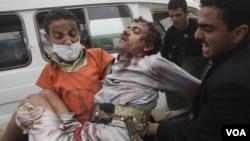Para demonstran anti pemerintah di Sana's menolong rekan mereka yang terluka setelah terkena tembakan pasukan keamanan Yaman (24/11).