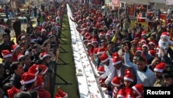 People pose next to a 76-meter (251-foot-long) cake during Christmas celebrations at a consumer fair in Chandigarh, India, Dec. 25, 2015.