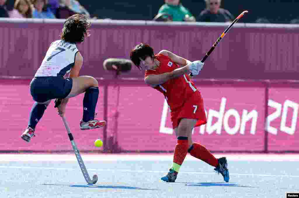Japan's Shiho Otsuka (L) challenges South Korea's Lee Seonok in their women's Group A hockey match.