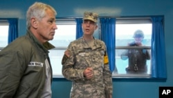 Secretary Hagel listens to U.S. Army Col. James Minnich as a North Korean soldier takes a photograph of the secretary through a window, Sept. 30, 2013.
