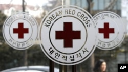 A pedestrian moves past the logos of the Korea Red Cross at its headquarters in Seoul, South Korea, Wednesday, Feb. 9, 2011. South Korea agreed Wednesday to hold talks with North Korea on reuniting families separated by war, as military officers from both