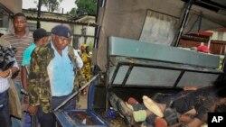 Afisa wa polisi akilinda maiti za watu sita walouliwa waliposhambulia kambi ya jeshi Mombasa, Kenya Jumapili Nov 2, 2014