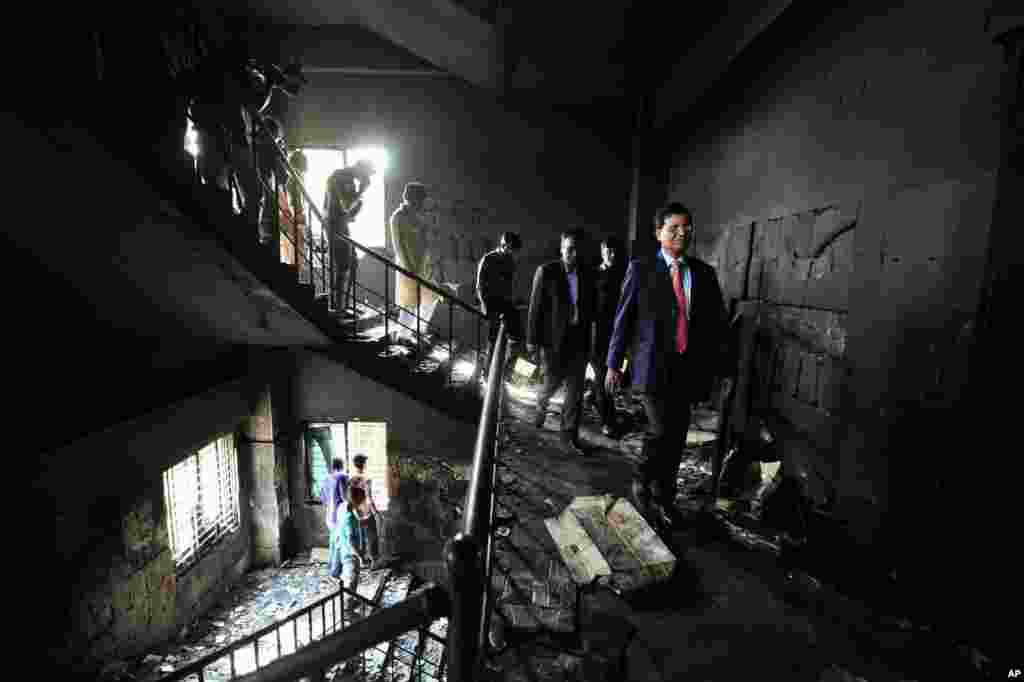 Bangladeshi officials inspect a garment-factory where a fire killed more than 110 people Saturday on the outskirts of Dhaka, Bangladesh, November 26, 2012.