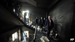 FILE - Bangladeshi officials inspect a garment-factory where a fire killed more than 110 people Saturday on the outskirts of Dhaka, Nov. 26, 2012.