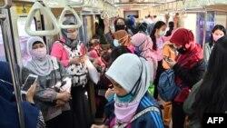 Para penumpang perempuan mengenakan masker di tengah wabah virus corona (Covid-19) di gerbong kereta commuter, di Jakarta, 7 April 2020. (Foto: AFP)