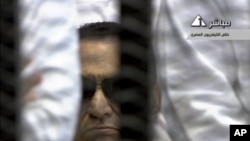 In this video image taken from Egyptian State Television, 84-year-old former Egyptian president Hosni Mubarak is seen in the defendant's cage as a judge reads the verdict in on charges of complicity in the killing of protesters during last year's uprising
