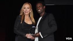 Сюзан Кармел Лерман получает награду из рук участника программы Фулбрайта из Уганды