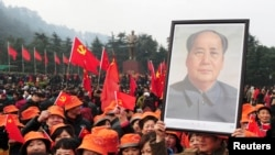 FILE - A man holds up a portrait of the late Chairman Mao Zedong as he and others gather in front of a giant statue of Mao to celebrate the 120th birth anniversary of the former leader, in Shaoshan, Mao's hometown, Dec. 26, 2013.