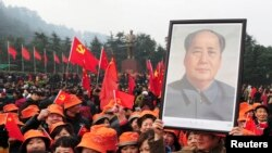 Warga China membawa potret mendiang Mao Zedong dalam peringatan hari kelahiran ke-120 di kota Shaoshan, tempat kelahiran Mao, Kamis (26/12).
