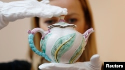 FILE - A Sotheby's employee poses with a Chelsea scolopendrium-molded teapot (dated c.1750), believed to be the only surviving example of this pattern, at Sotheby's auction house in London, May 9, 2014.