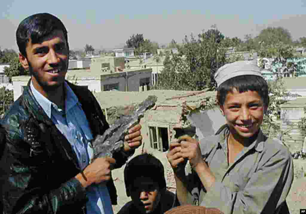 穆哈穆德•安瓦尔(左)与一名不知名的男孩2001年10月8日在喀布尔展示弹片。