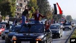 Partidarios del gobierno sirio ondean bandeas nacionales y entonan eslóganes contra el presidente esatdounidense Doland Trump durante manifestaciones tras ataques de EE.UU., Francia y el Reino Unido en Siria.