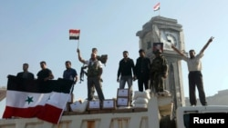 Fighters loyal to the Assad regime hold up the Syrian national flag stand June 5, 2013 after capturing the town of Qusair from anti-government rebels.