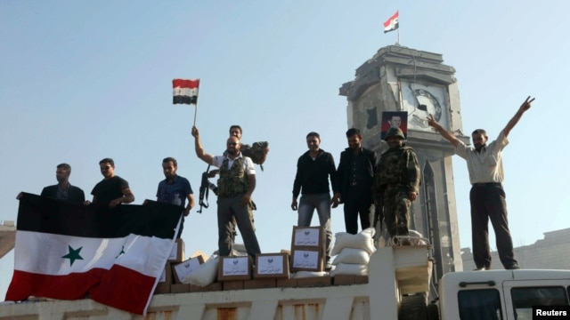 Fighters and civilians loyal to the Assad government hold up the Syrian flag after capturing the strategic town of Qusair, June 5, 2013.