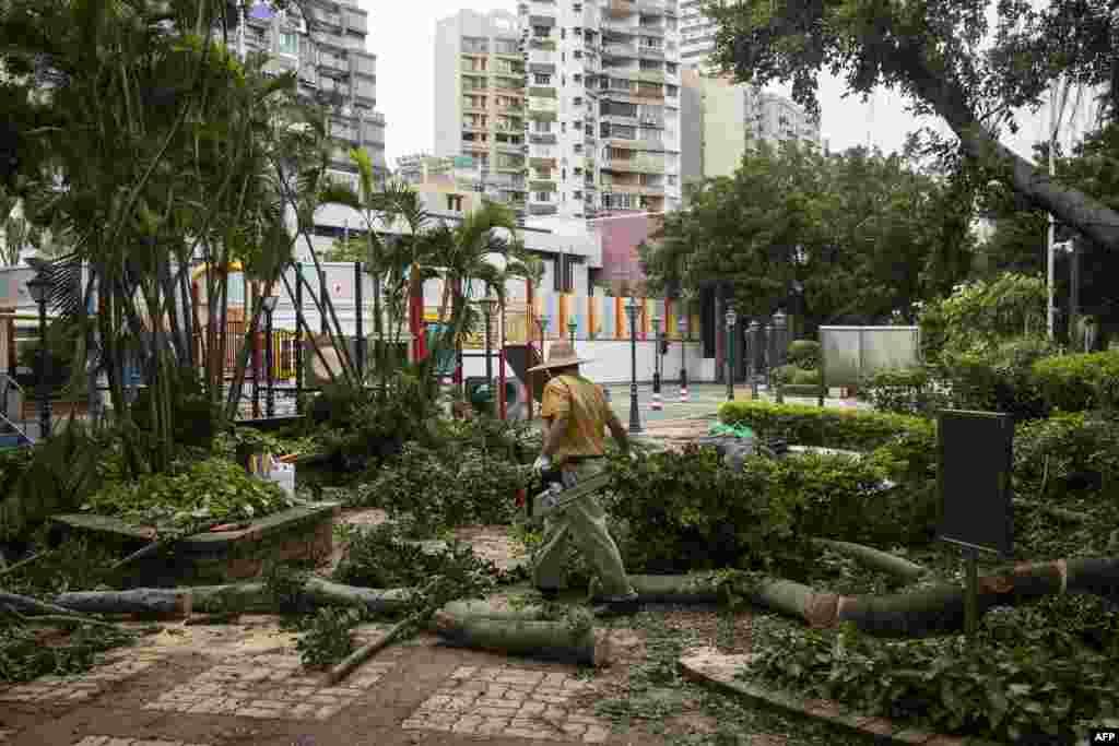 """2018年9月17日台风山竹袭击澳门后,一名工人在操场上清理树枝。美国国务卿蓬佩奥表示:""""我们惦记那些受台风'山竹'影响的人并为他们祈祷,同时我们向遇难者的家属及至爱亲朋表示哀悼。"""""""