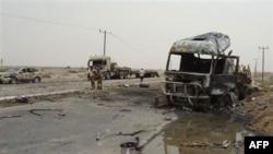 Binh sĩ Yemen bên cạnh một chiếc xe quân sự bị thiêu rụi tại hiện trường một vụ tấn công ở Aden, Yemen, ngày 24/7/2011