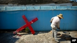 FILE - A church member shovels cement mix preparing to re-mount a cross on a Protestant church, which had been forcibly pulled down by Chinese government workers, in Taitou Village, eastern China, July 29, 2015.