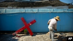 A church member shovels cement mix preparing to re-mount a cross on a Protestant church, which had been forcibly pulled down by Chinese government workers in Taitou Village, eastern China. (file)