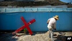 2015年7月29日,中國東部一村莊的一名基督教信眾在和水泥,準備重新架起被政府當局強拆的十字架(資料圖片)