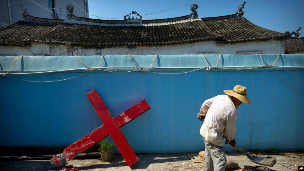 2015年7月29日,中國東部一村莊的一名基督教信眾在和水泥,準備重新架起被政府當局強拆的十字架(資料圖)