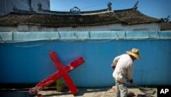 Một giáo dân đang dùng xi măng để dựng lại cây thánh giá bị nhân viên chính phủ Trung Quốc cưỡng ép tháo xuống tại nhà thờ Protestant ở làng Taitou, phía đông Trung Quốc, ngày 29/7/2015.