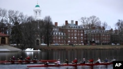 FILE - Rowers pass the campus of Harvard University as they move down the Charles River in Cambridge, Mass., March 7, 2017. Harvard and the group Students for Fair Admissions will go to trial in a lawsuit alleging discrimination against Asian-American ap