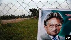 Sebuah poster mantan Presiden Pakistan Pervez Musharraf terlihat terpasang di pintu gerbang rumahnya yang dijaga ketat di Islamabad, Pakistan, 6 November 2013 (Foto: dok). Ancamam bom membuat sidang pertama terhadap Musharraf ditangguhkan pelaksanaannya, Selasa (24/12).