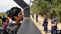 15일 세르비아의 헝가리 접경 호르고스에서 난민들이 철책 넘어 헝가리 쪽을 바라보고 있다.