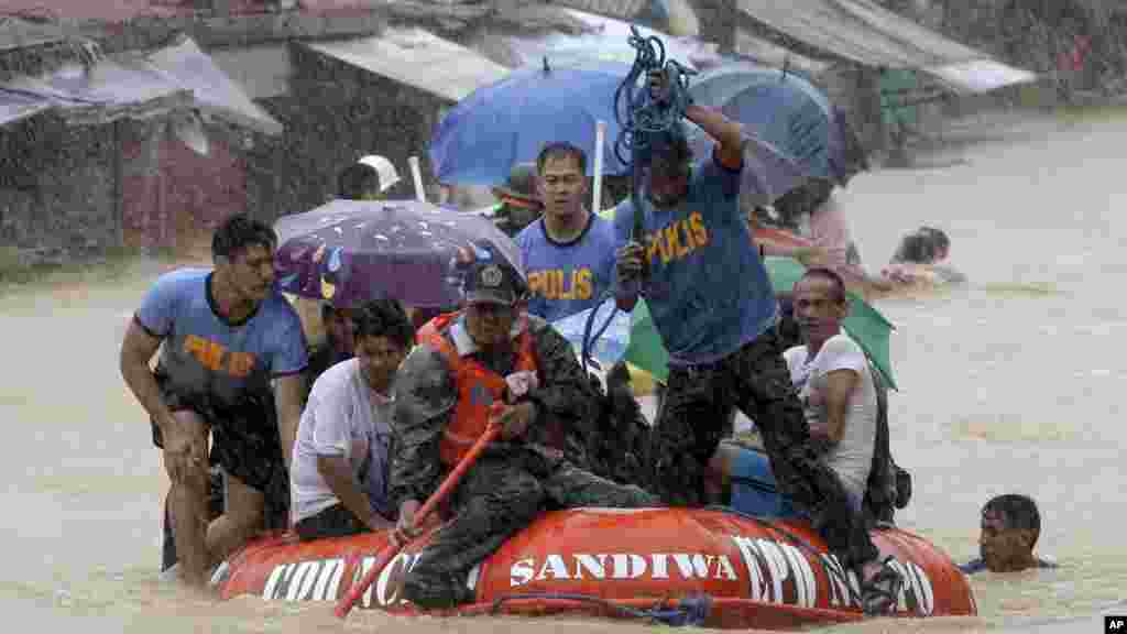 A man dives in the background as rescuers use a rubber dinghy to rescue trapped residents after continues heavy monsoon rains spawned by tropical storm Fung-Wong flooded Marikina city, east of Manila, Philippines, and most parts of the metropolis, Sept.