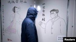 一名工作人員戴著防護面具經過在湖北省武漢市雷神山醫院封閉病房內的素描牆,牆上畫著中國國家主席習近平的素描照。 (2020年4月11日)