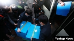 자원개발 비리 의혹을 수사 중인 서울중앙지검 특수1부 관계자들이 18일 경남기업 본사에서 압수품을 차에 싣고 있다.