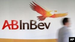 FILE - A man walks past the AB InBev logo in Leuven, Belgium.