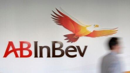 FILE - A man walks past the AB InBev logo in Leuven, Belgium.