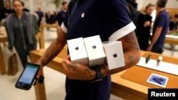 Seorang karyawan menunjukkan ponsel iPhones X di sebuah Apple Store di Regents Street, London, Inggris, 3 November 2017.