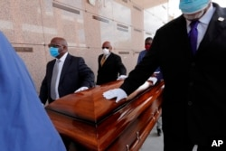 In this April 22, 2020, file photo, pallbearers, who were among only 10 allowed mourners, walk the casket for internment at the funeral for Larry Hammond, who died from the coronavirus, at Mount Olivet Cemetery in New Orleans.(AP Photo/Gerald Herbert, File)