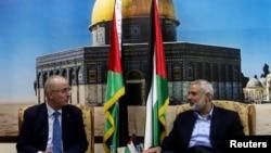 Senior Hamas leader Ismail Haniyeh (R) speaks with Palestinian Prime Minister Rami Hamdallah at Haniyeh's house in Gaza City, Oct. 9, 2014.