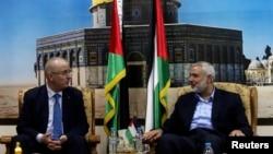 Pemimpin Hamas Ismail Haniyeh (kanan) berbicara dengan PM Palestina Rami Hamdallah di Gaza (9/10).