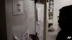 FILE - Pharmacist Mary Chindanyika labels a fridge containing a trial vaccine against HIV on the outskirts of Cape Town, South Africa, Nov. 30, 2016. The latest attempt in the long, frustrating search for a vaccine against HIV has begun in South Africa.