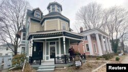 Kate and Cameron Reinhart stand on the porch of their 1880's Octagon house they are renovating during the coronavirus pandemic, in Norwich, eastern Connecticut, U.S., January 14, 2021. (REUTERS/Dan Fastenberg)