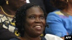 FILE - Simone Gbagbo, Ivory Coast's former first lady, smiles as she sits in the dock at the Court of Justice in Abidjan on Dec. 26, 2014, for the start of her trial.