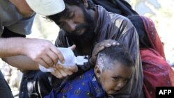 An American nurse from the Save the Children non-governmental organization treats a Pakistani baby injured in the earthquake in Pashto area in the mountains in the north of the country. (File Photo)